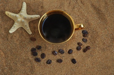 3407627-gold-cup-with-coffee-beans-and-starfish-on-a-sea-beach