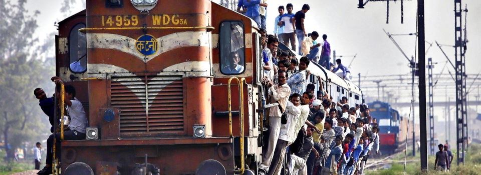 Passengers travel on an overcrowded train at Loni town in Uttar